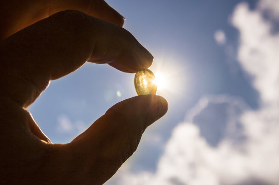 Hand holding soft ged fish oil or vitamin d capsule against blue sky and sun. Sun vitamin concept.