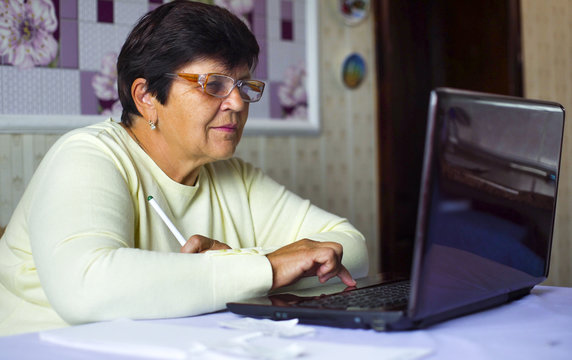 Senior old woman in eyeglasses surfing internet on laptop at home. White caucasian female pensioner using computer shopping online. Technology, communication, information concept