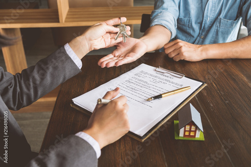 Real Estate Agent Are Giving House Keys To Customer After Sign
