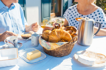 Bread basket with rolls and croissants on table in summer garden while two senior people having breakfast outdoors