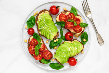 healthy avocado and tomatoes sandwiches with hummus, sesame and basil in a plate with fork