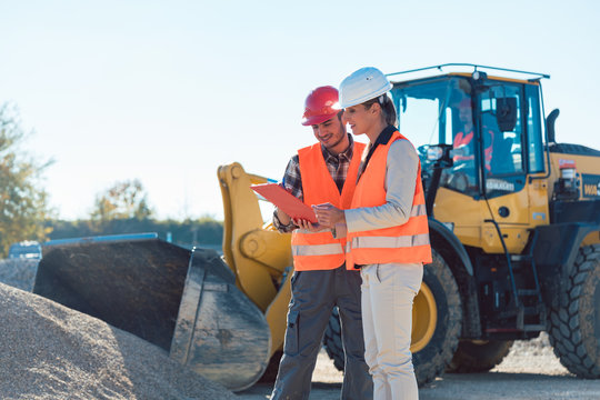 Man and woman worker on construction site talking
