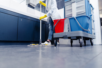 Low shot of cleaning lady mopping the floor in restroom beside her trolley