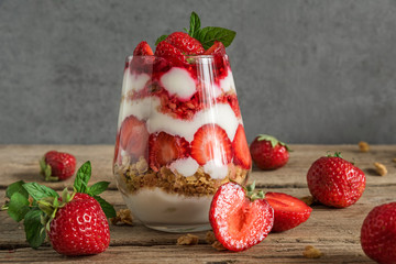 strawberry yogurt parfait with granola, mint and fresh berries in a glass on rustic wooden table....