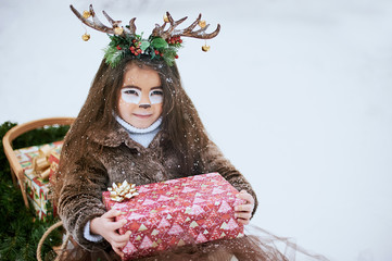 Fairy tale girl. Portrait a little girl in a deer dress with a painted face in the winter forest. Big brown antler