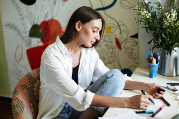 Young beautiful girl sitting at the desk dreamily drawing with colorful felt-tip pens at cozy home