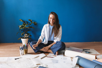 Smiling painter sitting on floor with drawings near over blue background at home