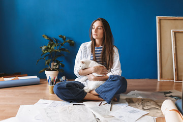 Pensive girl sitting on floor with drawings holding cute white cat in hands while thoughtfully looking aside at home