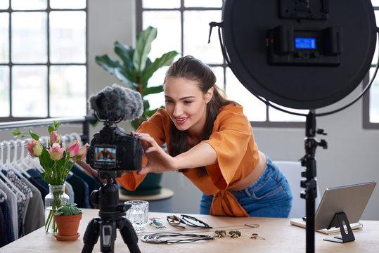 Online content creator vlogger adjusting her recording equipment