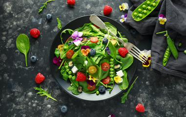 Summer salad with edible flowers, spinach, blueberries, raspberry, sweet peas, cherry tomatos and feta cheese