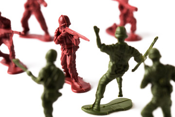 Toy soldier shooting an enemy in a toy battle, isolated on white background