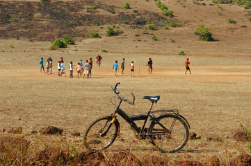 lonely standing bicycle. old bike in the field on which boys play cricket