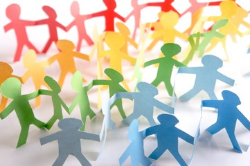 Paper people holding each other in LGBT rainbow colors