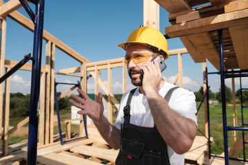 The man builder on the background of the roof frame house, in a yellow helmet and gray overalls uses a mobile phone.