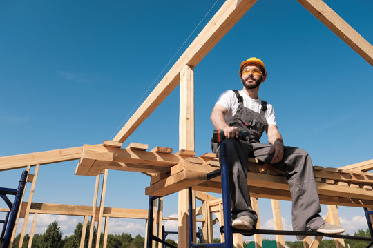 The man builder sits on the edge of the roof of the frame house, in a yellow helmet and gray overalls. The blue sky and clear sunny day.