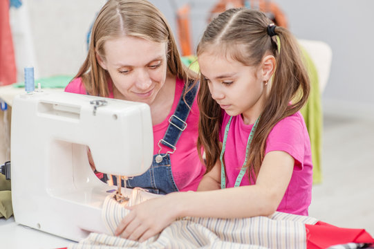 Mother teaches a little girl to sew on a sewing machine