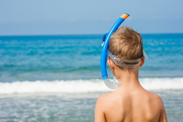 Boy in snorkelling mask. Back view. Space for text