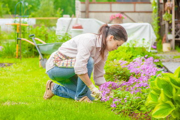 Happy woman planting flowers at back yard