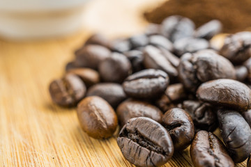 close-up coffee beans with cup on wooden rustic board