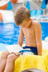 Little boy reading a book on the beach.  Relaxation resting vacations concept