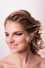 Brown-haired woman with wedding hairstyle and makeup smiles against the background of a vintage wall close-up.