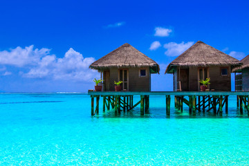 Photo sur Plexiglas Bleu fonce Water villas on wooden pier in turquoise ocean on the white sand beach