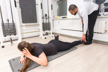 Personal instructor training with woman at gym