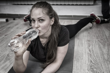 Woman drinking water while lying on mat at gym