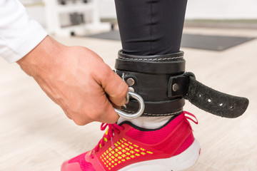 Hand Clipping Fastener to Ankle Strap in Gym
