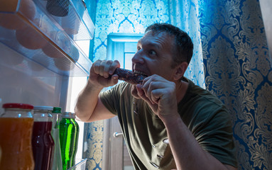 Hungry man snacking on salami from his fridge
