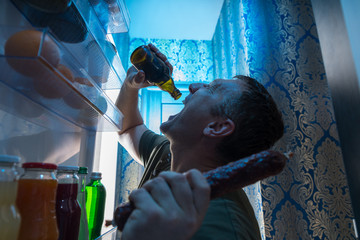 Thirsty man drinking cold beer from his fridge