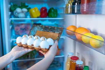 Person taking fresh eggs from fridge