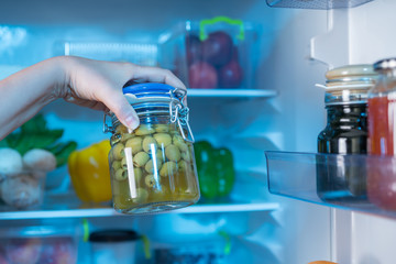 Hand holding jar with green olives against fridge