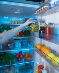 Hand reaching for jar with green olives in fridge