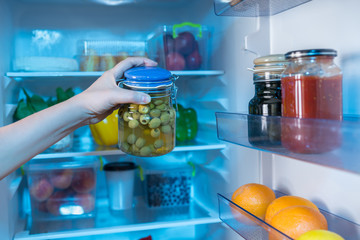Hand reaching for jar with olives in fridge