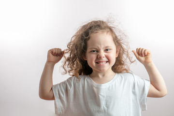 angry girl with long red wavy hair shoeing her strength. funny girl with raised arms demonstrating her biceps. bodybuilding, sport concept
