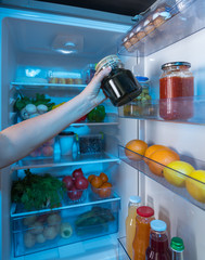 Hand reaching for jar of preserves in fridge