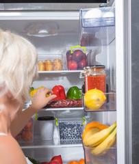 Woman opening fridge full of fresh food