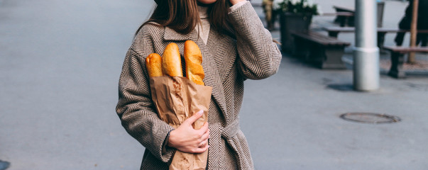 a girl in a coat and hat holds a bag with baguettes, bread, a loaf, on the street. a shopping trip, morning. Wall mural