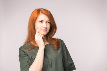 Attractive thinking red-haired woman on white background
