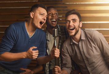Happy friends singing karaoke together in bar Fotobehang