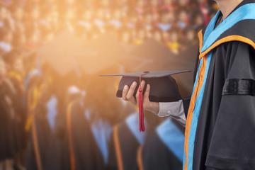 Graduates hold a congratulatory hat on campus.