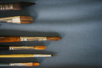 Artist's brush on the fabric, top view and close-up. Creative tools ready for use on the table. Soft focus.