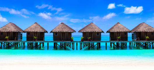 Wall Mural - Water villas on wooden pier in turquoise ocean on the white sand beach