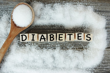 Diabetes word on wooden letters with crystalized white sugar as frame