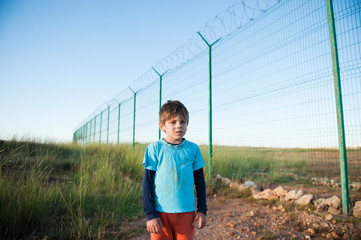 suffering refugee child with dirty face near fence on state border in desert