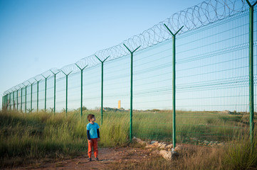 lonely little kid refugee watching at high fence with barbed razor wire desert