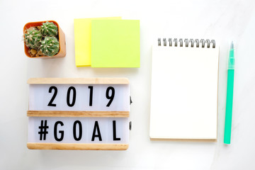 2019 goals on wood box and blank notebook paper on white marble background, business new year aim to success