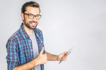 Happy young man in plaid shirt standing and using tablet over grey background. Sign super.