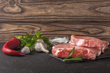 raw fresh steak with salt, spices and rosemary on black stone